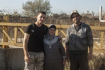 """Hiyam Ahmad Jumaa, and her two sons in front of """"Barrier Gate 105"""", outside of Beit Surik village (Ramallah), 31 October, 2019. ©  Photo by OCHA"""
