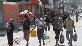 IDPs in their way to a shelter, Ash Shuja'iyeh area, Gaza City, August 2014. Photo by OCHA