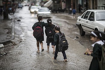 Children on their way back from school, during floods in Gaza city, January 2015. © Photo by Wissam Nassar