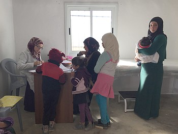 Amal and her sister-in-law and their children receiving treatment at al Mirkez mobile clinic. Photo by OCHA