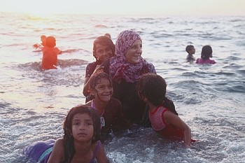 Ahlam joining her children in swimming at the beach.  Dear Al Balah Camp. © Photo Credit: Rehaf Batniji/OXFAM 2018