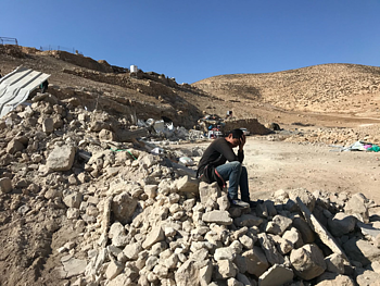 Young boy in front of his demolished home in Maghayir al Abeed (Hebron), 5 December 2019. ©  Photo by OCHA.