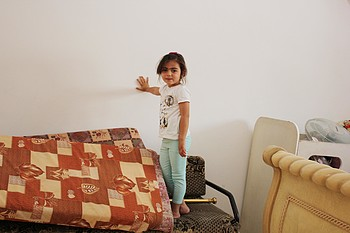 Suhad's daughter, Muluk (4 years old), standing in her repaired bedroom.