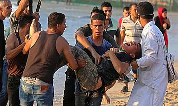 פלסטיני שנפצע בהפגנה נגד המצור הימי על החוף בקרבת הגדר מצפון־מערב לבית לאהיה, ספטמבר 2018. צילום: אשרף עמרה