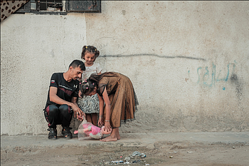 Rimas, 7, and Layan, 11, play with their father Medhat, 33, outside their home in Jabalia on 21 August 2019. ©  Photo by Ahmed Mashharawi, NRC