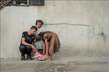 רימאס בת השבע ולָיאן בת ה־11 משחקות עם אביהן מדחת, בן ה־33, מחוץ לביתן בג׳באליה, ב־21 באוגוסט 2019 / © צילום: אחמד משחראווי, מועצת הפליטים הנורבגית