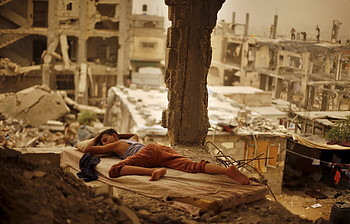 Palestinian boy sleeping inside his destroyed home in the Shuja'iyeh neighbourhood of Gaza City, September 2015. ©  Photo by Suhaib Salem