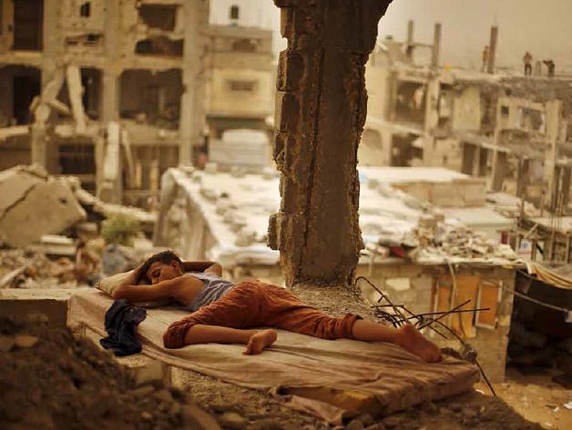 Palestinian boy sleeping inside his destroyed home in the Shuja'iyeh neighbourhood of Gaza City, September 2015. Photo by Suhaib Salem