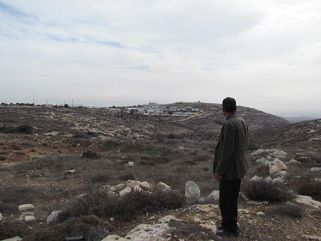 Ahmad Abu Shanab looking at his land near Pnei Kedem outpost, Nov 2014. © Photo by OCHA