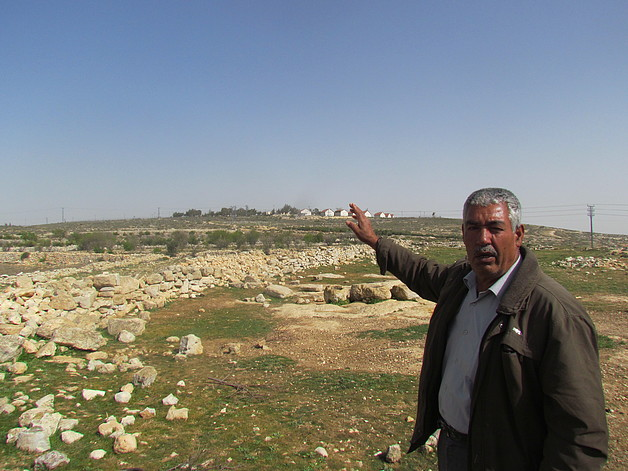 Farmer from Sa'ir pointing at his land next to Asfar settlement