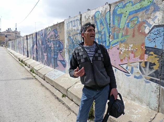 Abu Shamsiyyi standing by the wall outside his house in Tel Rumeida, Hebron, March 2017. Al Shuhada Street, Hebron city, March 2017. ©  Photo by OCHA.