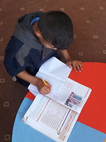 عبد الله ينجز واجباته البيتية في مركز الحماية التابع لمؤسسة أرض الإنسان  © - تصوير مؤسسة أرض الإنسان