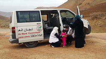 אנשי רפואה העובדים עם איחוד ועדות הבריאות מטפלים בילדה באזור אל־מאלח. צילום: ארגון הבריאות העולמי/אליס פלייט