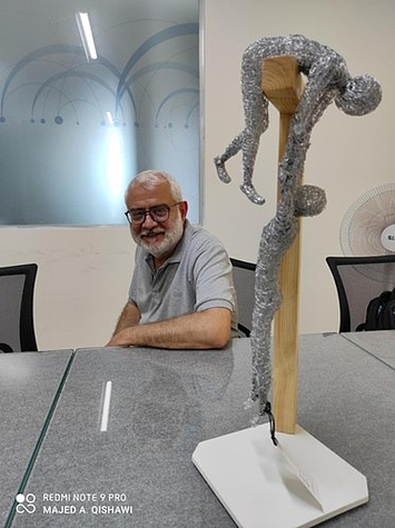 Dr. Mustafa Al-Masri with an art piece made by a patient who survived attempted suicide