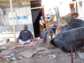 אבו מוחמד ומשפחתו ליד המחסה הזמני המאולתר שלהם בבית חנון, מאי 2015 / © צילום: משרד האו״ם לתיאום עניינים הומניטריים