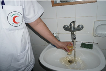 Medical staff showing rusty water available through water network, Al Shifa hospital, Gaza. November 2018