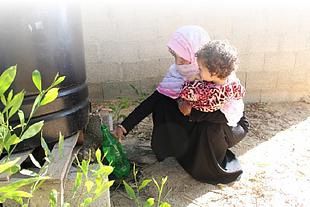 منى وهي تملأ زجاجة من المياه غير الصالحة للشرب من خزان في ساحة منزلها. © - تصوير منظمة أوكسفام