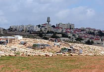 Houses in the Palestinian Bedouin community of Arab al Jahalin al Jabal, east of Jerusalem, against the backdrop of the Israeli settlement of Ma'ale Adummim. © Photo by OCHA.
