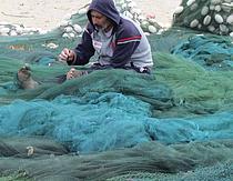Gaza fisherman working on his nets Gaza fishing wharf. Gaza city, April 2013. Photo by OCHA