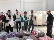 Staff of an aid organization preparing for the distribution of bedding sets to isolation centers. April 2020, Rafah. Photo by NRC
