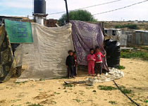 Children standing in front of a temporary shelter made of cloths in Gaza, January 2016