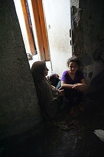 Abeer al Nemnem and her daughters sitting at the porch of their house in Ash Shati Refugee Camp, Gaza, May 2017. ©  Photo by OCHA.