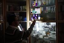 Pharmacist using emergency light, Gaza 27 April 2017. © Photo by OCHA.