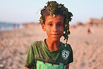 Palestinian boy after swimming in a polluted beach in Deir al Balah Camp, Gaza. © Photo Credit: Rehaf Batniji/OXFAM 2018