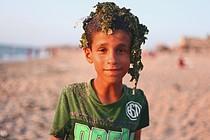 فتى فلسطيني بعد أن سبح على شاطئ ملوث في مخيم دير البلح للاجئين، غزة © - تصوير رهف بطنيجي، منظمة أوكسفام، 2018