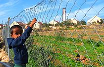 محمد، ابن عزيز )ست سنوات(، يقف بالقرب من بستان الخضار الصغير الخاص بهم في أم الخير، حزيران/يونيو 2015 .صورة بواسطة برنامج الأغذية العالمي/كولن كامبشوير
