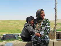 Shifaa Abu Iram and her son sitting in Halaweh community, Massafer Yatta (Firing zone 918).  © Photo by OCHA