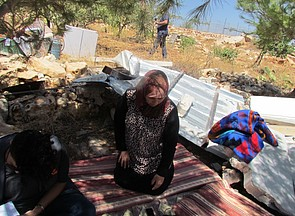 A Palestinian mother of four, resident of Jourat al Khiel, sitting on the belongings of her family following the demolition of their home by the Israeli authorities on 16 August 2016