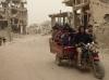 أطفال يركبون عربة وخلفهم مباني مدمرة جراء الأعمال القتالية، الشعف في منطقة التفاح، غزة، شباط/فبراير 2015,تصوير مكتب تنسيق الشؤون الإنسانية