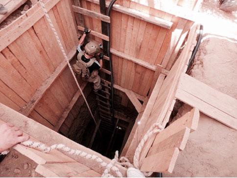 قام فني من دائرة الأمم المتحدة للأعمال المتعلقة بالألغام، في 18 تموز/يوليو 2016، بالنزول في حفرة خلال عملية إزالة لقذيفة جوية غير متفجرة مدفونة عميقا في الأرض. صورة بواسطة دائرة الأمم المتحدة للأعمال المتعلقة بالألغام